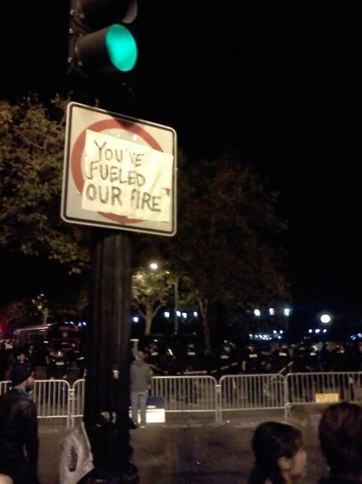 Sign says you've fueled our fire. Riot police stand behind
