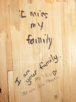 """We are all your family"" written on the wall of the Embrace statue"