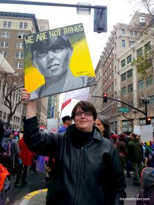 Protestor at Oakland Woman's march whose sign is a painting of a woman and the ltters WE ARE NOT THINGS