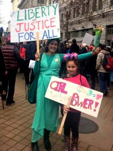 Woman dressed as Statue of Liberty with girl holding Girl Power sign