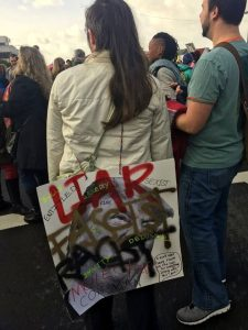 """""""Liar, fascist, racist, molestor, con man..."""" this sign lists all of Trump's flaws, with a speech bubble that says, """"I can't fit everything wrong with this jerk on one sign!"""""""